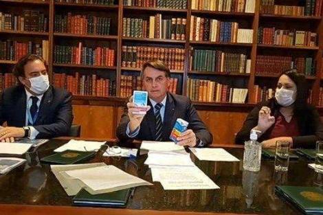 O presidente Jair Bolsonaro exibe caixas do medicamento cloroquina durante live transmitida pelo Facebook